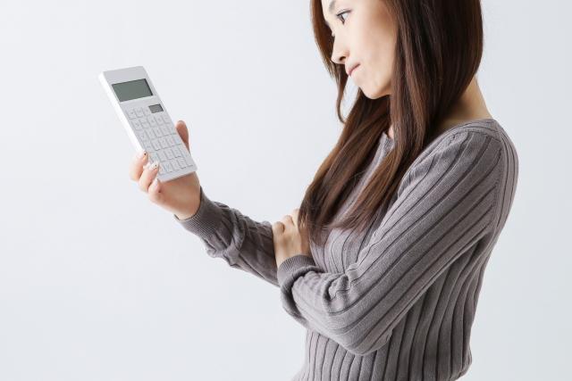 電卓を見て悩む女性