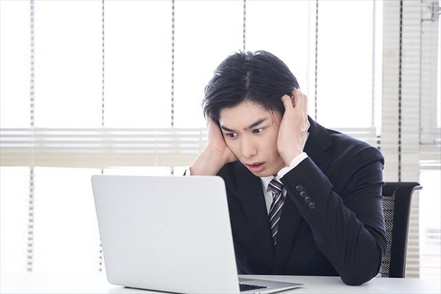 パソコンを見て驚く男性